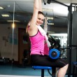 Stock Photo: Womtoning her upper and core muscles in multi gym