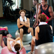 Stock Photo: Trainer instructing gym clients on how to use exercise ball