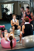 Trainer instructing gym clients on how to use exercise ball — Stock Photo
