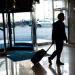 Man entering hotel lobby with his luggage — Stock Photo #13537379