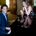 muž hrát na klavír a zábavné svého společníka drží koktejl — Stock fotografie