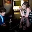 Woman enjoying cocktail and admiring man playing piano — Stock Photo