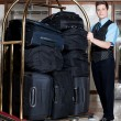 Concierge with a pile of bags in luggage cart - Foto Stock