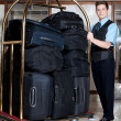 Concierge with a pile of bags in luggage cart - Stok fotoğraf