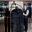 Bell boy pushing cart loaded with luggage — Stock Photo
