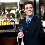 Veselá výkonný pózuje s lahví vína — Stock fotografie