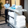 Active worker pushing housekeeping cart around lobby — Stock Photo #13537710
