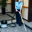 Staff cleaning carpet with a vacuum cleaner — Stock Photo