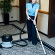 Staff cleaning carpet with a vacuum cleaner - Stock Photo
