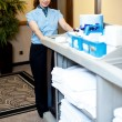 Beautiful employee psuhing housekeeping cart — Stock Photo