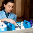 Stock Photo: Pretty female housekeeper busy working