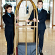 Concierge colleagues holding baggage cart — Stock Photo