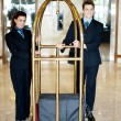 Stock Photo: Concierge colleagues holding baggage cart