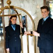 Stock Photo: Concierges holding cart and posing