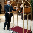 Casual shot of a concierge pushing the cart — Stock Photo