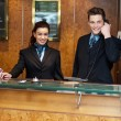 Male and female at hotel reception busy working - Stock Photo