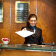 Female receptionist handing over check-out papers — Stock Photo