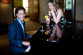 Man playing piano and entertaining his companion holding cocktail — Stock Photo