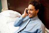 Young man conversing on mobile phone — Stock Photo
