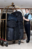Concierge with a pile of bags in luggage cart — Stock fotografie