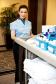Charming female executive holding toiletries cart — Stock Photo