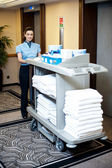An active worker pushing housekeeping cart around the lobby — Stock Photo