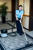 Staff cleaning carpet with a vacuum cleaner — Zdjęcie stockowe