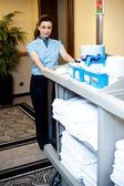 Beautiful employee psuhing housekeeping cart — Stock Photo