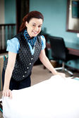 Beautiful smiling attendant holding sheet, redoing room — Stock Photo
