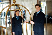 Concierges holding the cart and posing — Stock Photo