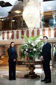 Executives posing under a chandler — Stock Photo