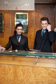 Male and female at hotel reception busy working — Stock Photo