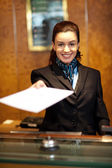 Cheerful female receptionist offering check-in papers — Stock Photo