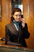Stylish female attendant at hotel reception — Stockfoto