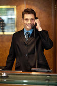 Cheerful front desk executive attending phone call — Stok fotoğraf