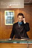 Profile shot of a handsome receptionist on the phone — Stockfoto