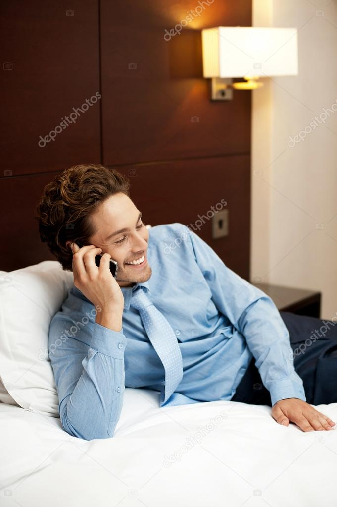 Delighted young man communicating with his partner on the phone. Relaxed in hotel room — Stock Photo #13537567