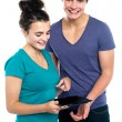 Gorgeous girl with her partner pointing at tablet pc — Foto Stock