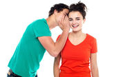 Handsome boy talking secret to young girl in her ear — Stock Photo