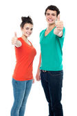 Teen love couple showing thumbs up to camera — Stock Photo