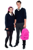 Boy holding pink backpack posing with female student — Stock Photo