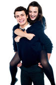 Cheerful boy carrying school friend on his back — Stock Photo