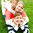 Husband, wife and child piled on each other — Stock Photo