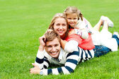 Smiling family of three piled on top of each other — Stock Photo