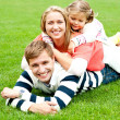 Young mother sandwiched between her daughter and husband — Stock Photo
