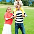 Cheerful family posing against nature background - Stock Photo
