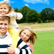 Family's day out in the park. Everyone enjoying - Stock Photo