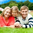 Couple lying in park with their daughter on top - Stock Photo