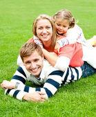 Jovem mãe imprensado entre sua filha e o marido — Fotografia Stock