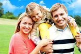 Beautiful happy caucasian family of three — Stock Photo